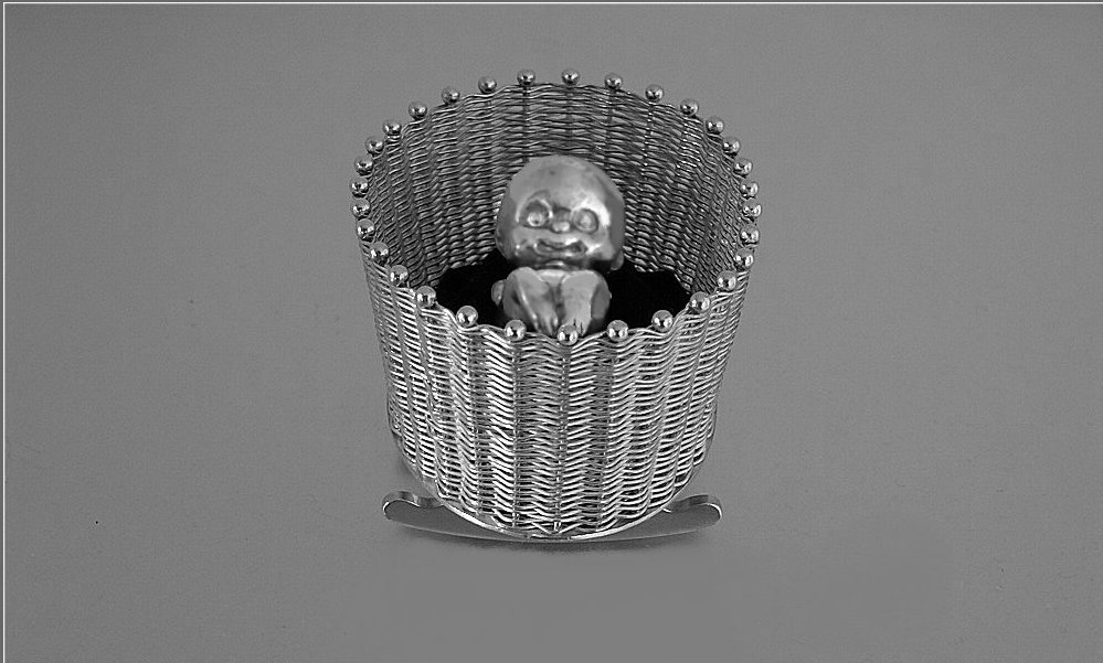 Rockable sterling silver woven crib and newborn baby